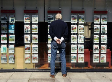 A man looks through the window of an estate agent in Dublin city
