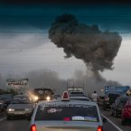 A traffic jam forms on a highway blocked because of a fire at a military depot near Chapaevsk in the Samara region of southern Russia. Exploding shells set off a fire that was triggering explosions Wednesday at a military depot in southern Russia, injuring about 30 people and causing the evacuation of more than 6,000 from a nearby village, investigators and emergency workers said. (AP Photo/Anatoly Bazhukov)