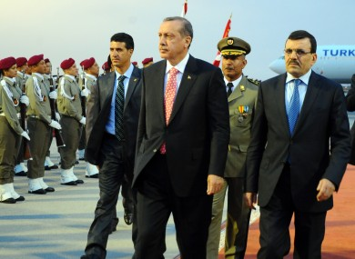 Tunisian Prime Minister Ali Larayed, right, greets his Turkish counterpart Recep Tayyip Erdogan, centre, at the Airport of Tunis Carthage, Tunis yesterday