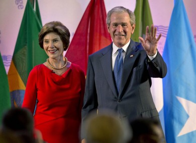 George W Bush on stage with his wife at the