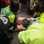 Kevin, 24 years old, from the US, is attended by medical assistants after he fell on the street during the third Valdefresno's bulls ranch run, at the San Fermin Fiestas in Pamplona northern Spain.(AP Photo/Alvaro Barrientos)