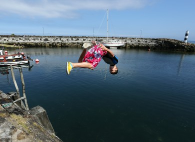 Teenagers jump into the harbour at Carnlough, county Antrim.
