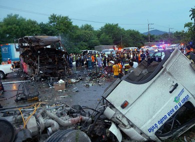 The charred wreckage of a double-decker passenger bus, top left, sits in the middle of a highway after a collision with a truck, foreground, in Saraburi province, northeast of Bangkok.