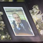 A portrait of the late broadcaster Colm Murray pictured in front of his coffin.<span class=