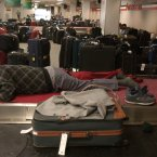 A stranded traveler sleeps in the baggage claim area at John F. Kennedy International Airport in New York. Ten years after a blackout cascading from Ohio affected 50 million people, utilities and analysts say changes made in the aftermath make a similar outage unlikely today, though shifts in where and how power is generated raise new reliability concerns for the U.S. electric grid system. (AP Photo/Julie Jacobson, File)