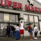 Customers line up outside of the Dallas Food Market to buy goods in Detroit, Mich(AP Photo/Paul Warner, File)