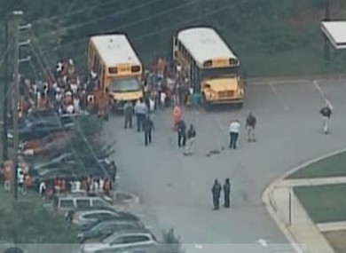 Children assemble outside the school after being evacuated from the building