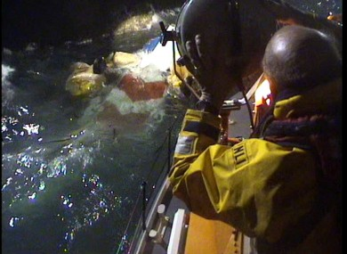 An RNLI volunteer shines a light on the helicopter wreckage in the early hours of this morning.