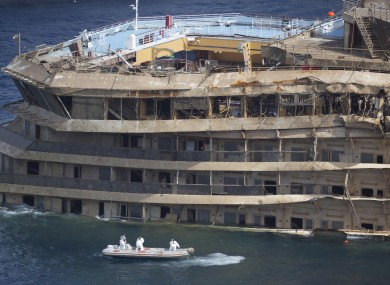 Workers on a boat sail past the Costa Concordia ship this week.