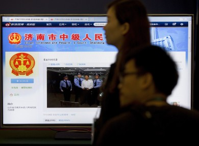 Journalists stand against a screen displaying a page from the Jinan Intermediate People's Court's website showing a photo of fallen politician Bo Xilai standing handcuffed as he is held by police at the court.
