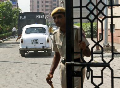 A policemen closes the gate of a court after a van, carrying the four men accused in the rape case enters.