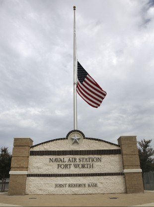The flag flies at half-staff at the front entrance of the Naval Air Station Joint Reserve Base in Fort Worth, Texas.