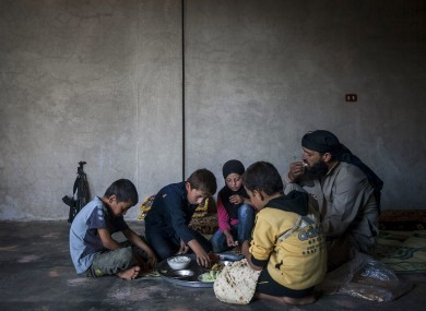 Ahmed al-Fikri sits with his sons and daughter, among them 12-year-old Abdo al-Fikri, second left, to eat lunch at their family house in Madaya village after school in the Idlib province countryside of Syria.
