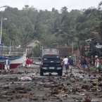 Debris litters the road by the coastal village in Legazpi city <span class=