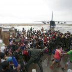 Survivors jostle to get a chance to board a C130 military transport plane.<span class=