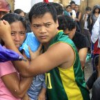 A husband and wife protect their newborn from the rain as they wait for an evacuation flight in Tacloban.<span class=