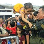 Philippine military personnel try to prioritise children and women first as they wait for evacuation flights in Tacloban.<span class=
