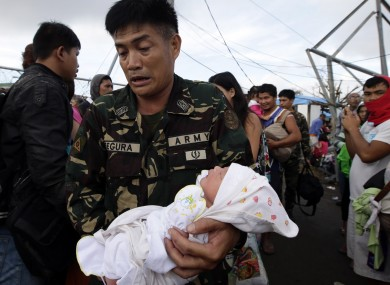 A soldier carries one-day-old baby Ian Daniel Honrado to a waiting military transport plane at Tacloban city, central Philippines.