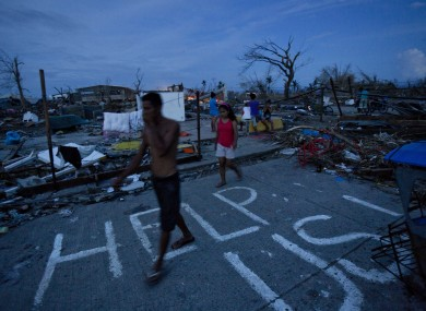 Typhoon Haiyan survivors walk through the ruins of their neighborhood in Tacloban