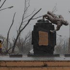 A young survivor uses a plastic cover to protect him from rain as he passes by a damaged Boy Scout statue at typhoon ravaged Tacloban city, Leyte province, central Philippines. Four days after Typhoon Haiyan struck the eastern Philippines, assistance is only just beginning to arrive. Authorities estimated the storm killed 10,000 or more across a vast swath of the country, and displaced around 660,000 others. <span class=