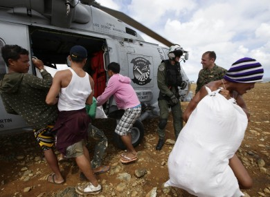 Trapped residents unload relief supplies from a U.S. Navy helicopter for villagers isolated by last week's super typhoon Haiyan.
