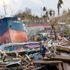A man passes through scenes of destruction in Tacloban.<span class=