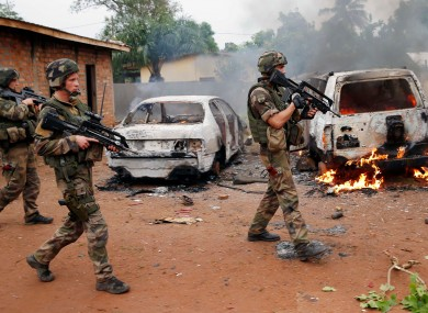 French troops patrol past two Seleka, the alliance of mostly Muslim rebel groups, vehicles set on fire by Christian mobs in Bangui.