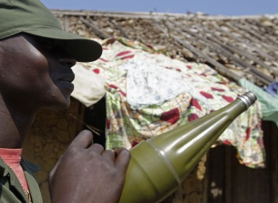 A heavily armed Congo trooper provides security, with others unseen, for villagers on the outskirts of Walikale, Congo