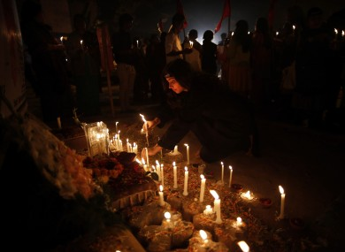 An Indian woman lights a candle to pay respect on the first anniversary of the fatal gang rape of the young woman in a bus New Delhi.