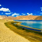 Travel to Pangong Tso Lake, a narrow saline lake in the Himalayas between India and Tibet. The bright blue water, contrasted by the mountains, is absolutely breathtaking.
