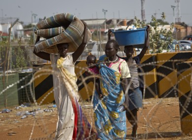 Displaced women carry belongings after seeking refuge at the compound of the United Nations Mission in South Sudan (UNMISS), in Juba, South Sudan