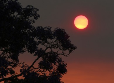 The sun glows a deep orange color as the light is filtered through smoke haze from wildfires drift over Sydney, Sunday, 20 October, 2013.