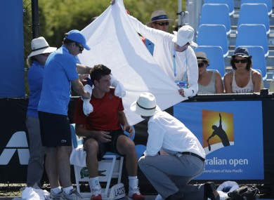 Frank Dancevic of Canada is protected from the sun after collapsing.