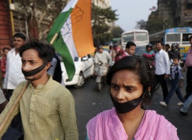 Activists of Indian National Congress with black bands around their mouth block traffic during a protest against a gang-rape and murder of a 16-year-old girl at Madhyamgram.