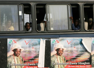 Commuters peer from a bus showing campaign posters of Dr Emmanuel Eweta Uduaghan a candidate for state governor in Port Harcourt Nigeria,