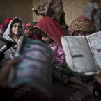 Pakistani children, whose families were displaced from Pakistan's tribal areas due to fighting between the Taliban and the army, hold booklets of Urdu alphabets and verses of the Quran, and repeat after their teacher, during their daily Madrassa, or Islamic school, at a mosque on the outskirts of Islamabad, Pakistan. <span class=