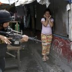 A resident cries as a SWAT member of the Philippine National Police searches for residents who allegedly threw rocks at them as they enforce the demolition of their shanties at the sprawling community of informal settlers at suburban Quezon city northeast of Manila, Philippines. The demolition, which saw the injury of at least four people, was carried out by the city government to pave the way for the commercial development of the area. <span class=
