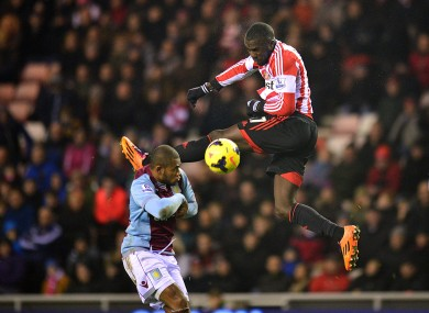 Sunderland's Jozy Altidore leaps to strike the ball alongside Aston Villa's Leandro Bacuna.