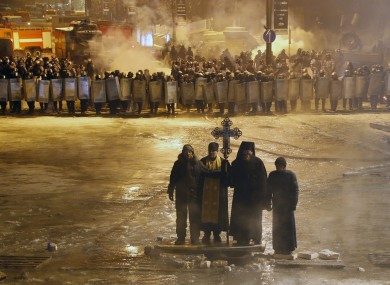 Orthodox priests pray as they stand between pro-European Union activists and police lines in central Kiev