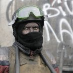 A protester guards the barricades in front of riot police in Kiev, Ukraine. The text reads 'War to palaces peace to home'. Ukraine's parliament is considering measures to grant amnesty to those arrested during weeks of protests in the crisis-torn country, but possibly with conditions attached that would be unacceptable to the opposition. <span class=