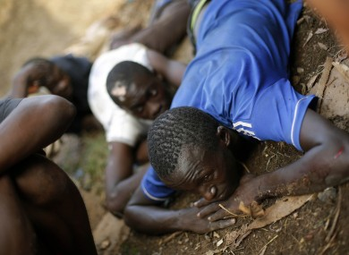 Men take cover as heavy gunfire erupts in the Miskin district of Bangui, Central African Republic