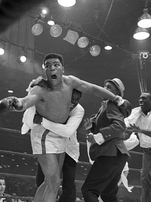 Cassius Clay's handlers hold him back as he reacts after he is announced the new heavyweight champion.