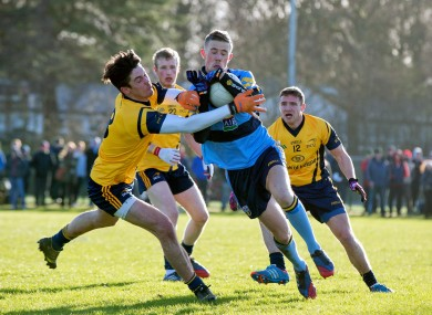 DCU's Eoin O'Connor challenges UCD's Paul Mannion.