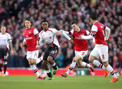 Liverpool's Daniel Sturridge (15) is challenged by Arsenal's Laurent Koscielny (6).