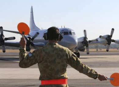 A Royal Australian Air Force AP-3C Orion is guided by a ground crew man on the tarmac at RAAF Base Pearce