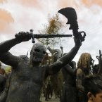 Mud-covered revellers attend the