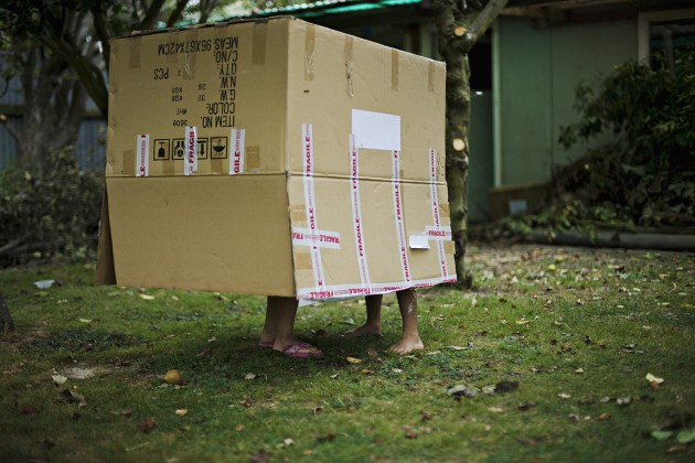 Children play in garden with cardboard box