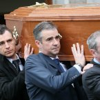 Son Darragh (back left) carries the coffin from the church. <span class=