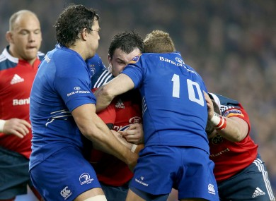 Leinster's Mike McCarthy and Ian Madigan tackle Damien Varley of Munster.