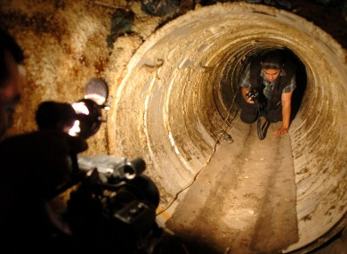 A federal agent climbs through a hidden tunnel between the US and Mexico.